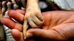 REUTERS Imagen de archivo. La madre de un niño de ocho meses con leucemia sostiene su mano.