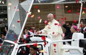 El papa Francisco es recibido por la gente, que le lanza pétalos de rosa, mientras recorre las calles de Quito en el papamóvil el 7 de julio de 2015. Francisco llega el miércoles a Bolivia tras pasar por Ecuador (AFP | Juan Cevallos)