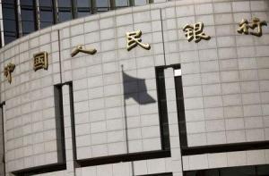 La sombra de la bandera nacional china en la sede del banco central del país en el centro de Pekín, el 24 de noviembre de 2014. El banco central de China dijo el jueves que no hay razones para que el yuan siga depreciándose, debido a los sólidos fundamentos económicos del país, en declaraciones que ayudaron a restablecer la calma en los agitados mercados globales después de que la entidad decidió devaluar la moneda a principios de la semana. REUTERS/Kim Kyung-Hoon/FIles