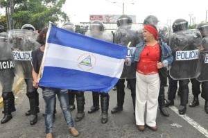 Estas dos mujeres manifestantes se pusieron a la par de los agentes del orden portando la bandera de Nicaragua en una marcha reciente reclamando elecciones justas y transparentes al CSE. Foto Ali B. del Castillo | CAWTV