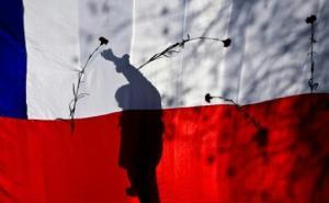 La sombra de un activista de derechos humanos se refleja sobre una bandera de Chile durante una protesta contra la dictadura de Augusto Pinochet (1973-1990), en Santiago, el 7 de septiembre de 2014 (AFP/Archivos | Martin Bernetti)