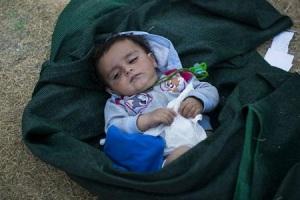 Un chico de dos años, duerme dentro de una manta en un campo de refugiados de Lesbos, en Grecia.  Foto:  Reuters