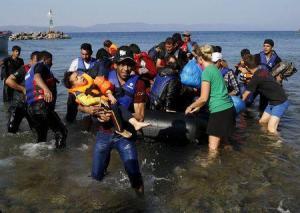 Un refugiado sirio carga a su hijo a su llegada a la isla griega de Lesbos tras una riesgosa travesía por mar desde las cortas de Turquía. REUTERS/Yannis Behrakis