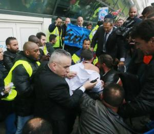 El director de recursos humanos de Air France, Xavier Broseta, centro, protegido por guardias de seguridad, trata de huir durante forcejeos con activistas sindicales el 5 de octubre del 2015 en el aeropuerto de Rossy, al norte de París. Los activistas protestan por las propuestas de eliminar empleos. (AP PFoto/Jacques Brinon)