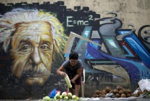 Un vendedor acomoda los vegetales para vender y detrás lo acompaña la caricatura de Albert Eistein, el 18 de septiembre de 2014, Filipinas. (AFP/Archivos | Noel Celis)