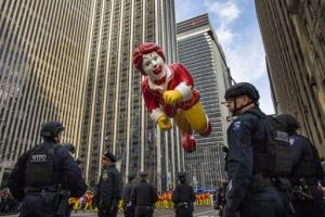 El globo de Ronald McDonald atraviesa Sixth Avenue entre policías armados que vigilan durante el tradicional desfile anual del Día de Acción de Gracias organizado por la tienda Macy's, el jueves 26 de noviembre de 2015. (Foto AP/Andres Kudacki)