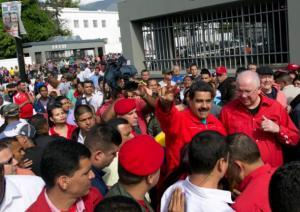 El presidente Nicolás Maduro hace la señal de la victoria al llegar a votar acompañado del embajador venezolano en las Naciones Unidas, Rafael Ramírez, durante los comicios para elegir una nueva Asamblea Nacional. (AP Foto/Alejandro Cegarra)