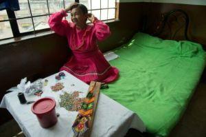Una indígena prepara artesanías para vender en Bogotá el 16 de diciembre de 2015 (AFP | Guillermo Legaria)