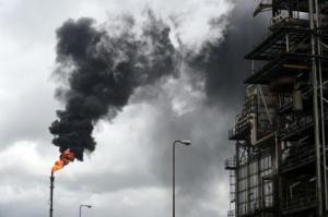 Gruesas olas de humo negro de una chimenea delgada como un lápiz en una refinería en Port Harcourt, en Nigeria, el 16 de septiembre de 2015. (AFP/Archivos | Pius Utomi Ekpei)