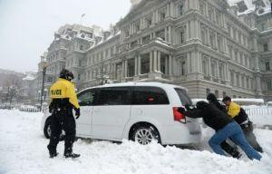 Policías empujan a un auto varado durante la tormenta de nieve en Washington el 23 de junio (AFP | Olivier Douliery)